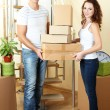 Young couple with boxes in new home — Stock Photo