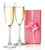 Glasses of champagne with gift box isolated on white — Stock Photo