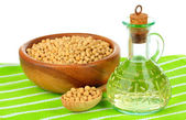 Soy beans and oil on table on white background — Stock Photo