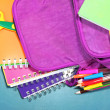 Purple backpack with school supplies on green desk background — Stock Photo #37260791