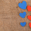 Hearts made of felt on sacking background — Stock Photo