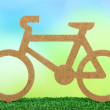 Decorative bicycle on grass on bright background — Stock Photo
