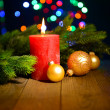 Composition with Burning candle, fir tree and Christmas decorations on multicolor lights background — Stock Photo #37269549