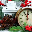 Clock with fir branches and Christmas decorations on table on wooden background — Stock Photo #37269569