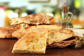 Pita breads on wooden stand with oil on table on bright background — Stock Photo
