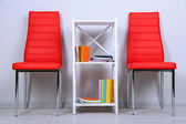 Beautiful interior with modern color chairs, books on wooden stand, on wall background — Stock Photo