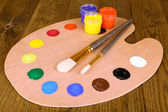 Wooden art palette with paint and brushes on table close-up — Foto de Stock