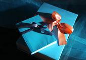 Libri avvolti con nastro di colore, sul tavolo di legno su sfondo scuro — Foto Stock
