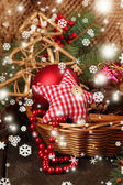 Christmas decorations in basket and spruce branches on table on brown background — Stock Photo