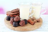 Tassen Eierlikör mit Süßigkeiten und Gewürze auf Tisch auf hellem Hintergrund — Stockfoto
