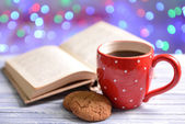 Composition of book with cup of coffee on table on bright background — Stock Photo