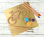 Decorative bicycle with drawing set on wooden background — Stock Photo