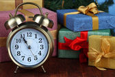 Alarm clock with presents on wooden table close up — Stock Photo