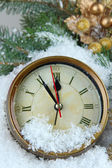 Clock with fir branches and Christmas decorations under snow close up — Photo