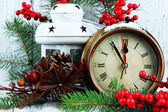 Clock with fir branches and Christmas decorations on table on wooden background — Stock Photo