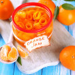 Orange jam with zest and tangerines, on blue wooden table — Stock Photo #37285957
