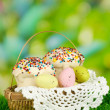 Easter cake with eggs in wicker basket on grass — Stock Photo