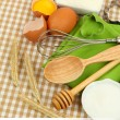 Cooking concept. Basic baking ingredients and kitchen tools on tablecloth background — Stock Photo #37286667