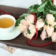 Beautiful bouquet of roses, on wooden tray, on light background — Stock Photo #37287093