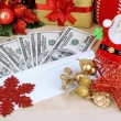 Dollar bills in envelope as gift at New year on wooden table close-up — Stock Photo #37289095