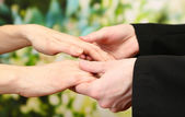 Priest holding woman hands, on green background — Stock Photo