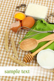 Cooking concept. Basic baking ingredients and kitchen tools on tablecloth background — Stock Photo