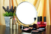 Round table mirror with cosmetics and flowers on table on fabric background — Stock Photo