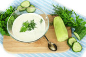 Cucumber yogurt in glass bowl, on color napkin, isolated on white — Stock Photo