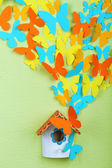 Paper butterflies fly out of nesting box on green wall background — Stock Photo