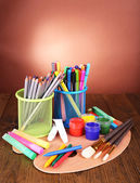 Composition of various creative tools on table on brown background — Stock Photo