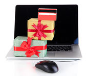 Laptop, gifts and computer mouse isolated on white — Stock Photo