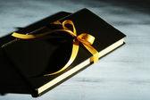 Libro avvolti con nastro di colore, il colore di sfondo in legno — Foto Stock