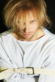 Homem doente mental no espartilho em fundo preto — Fotografia Stock