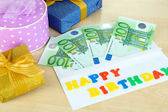 Euro banknotes as gift at birthday on wooden table close-up — Stock Photo