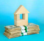 Wooden house on packs of dollars on blue background — Stock Photo