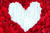 Beautiful heart of red rose petals on wooden table close-up — Stock Photo