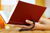 Hands with rosary and holy book, on light background — Stock Photo
