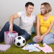 Young pregnant woman with her husband folding baby wear and ball on floor at home — Stock Photo