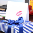 Gift with card for loved one on desktop on room background — Stock Photo #37291045