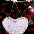 Blank heart and Christmas accessories on black background with lights — Stock Photo