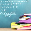 Stock Photo: Purple backpack with school supplies on wooden table on green desk background