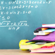 Purple backpack with school supplies on wooden table on green desk background — Stock Photo #37294269