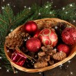 Christmas decorations in basket and spruce branches on wooden background — Stock Photo #37295619