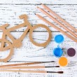 Decorative bicycle with drawing set on wooden background — Stock Photo #37297795