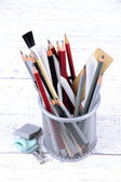 Professional art materials in metal holder, on wooden table — Stock Photo