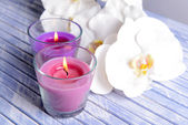 Beautiful colorful candles and orchid flowers, on color wooden table, on light background — Stock Photo