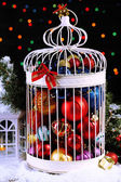 Christmas balls in decorative cage, on shiny background — Stock Photo