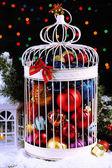 Kerstballen in decoratieve kooi, op glanzende achtergrond — Stockfoto