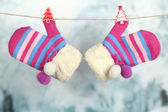 Striped mittens hanging on clothesline on bright background — Stock Photo