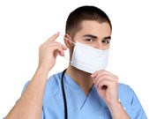 Young male doctor in medical mask, isolated on white — Stockfoto